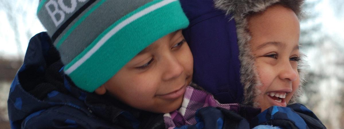 Kaksi tummaihoista lasta talvivaatteet yllään, lähikuva.