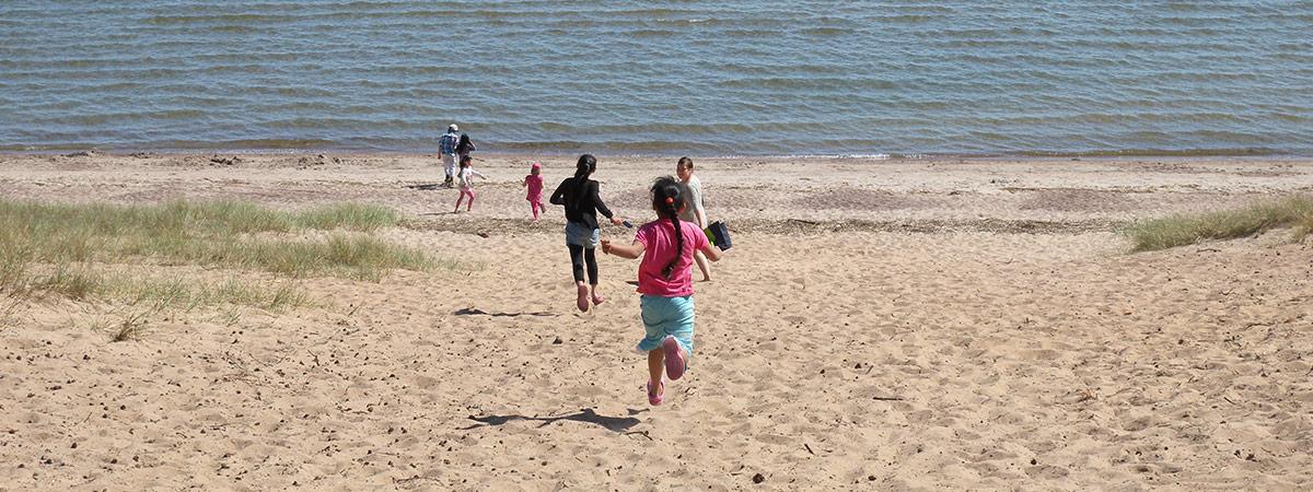 Ihmisiä juoksemassa hiekkarannalle.