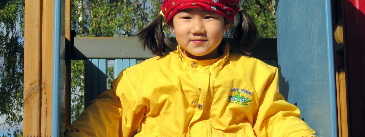 Pieni tyttö leikkipuistossa keltainen takki yllään.