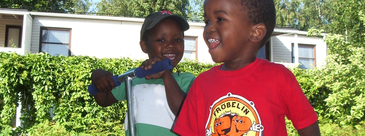 Kaksi tummaihoista poikaa potkulaudan kanssa talon edessä kesällä.