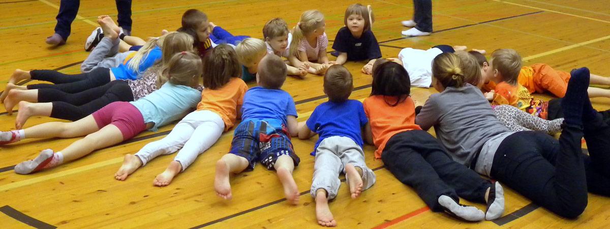 Lapset makaavat mahallaan ympyrässä liikuntasalissa.