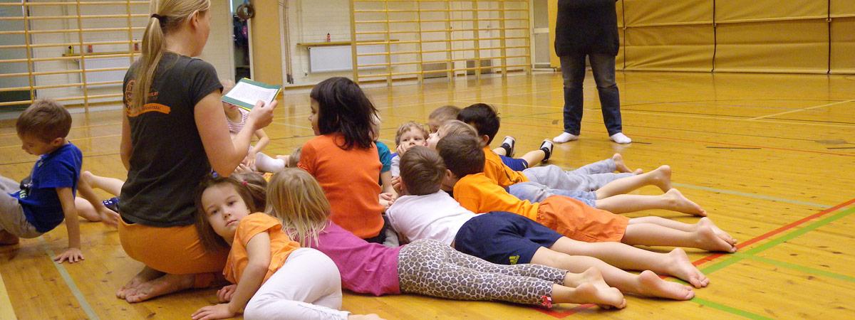 Lapsia liikuntasalissa aikuisen ympärillä.
