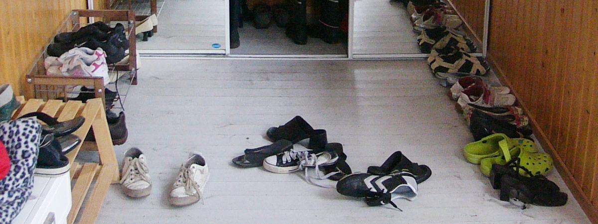 Eteisen lattia täynnä kenkiä.