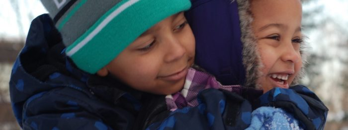 Kaksi tummaihoista lasta talvivaatteissa, lähikuva.