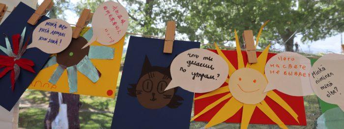 Narulle on ripustettu pyykkipojilla askarreltuja kortteja, joissa on tekstiä eri kielillä.