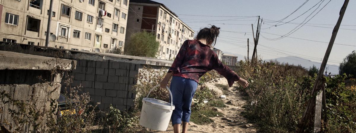 Romanialainen tyttö kantaa vesiämpäriä ränsistyneen kerrostaloalueen vieressä.