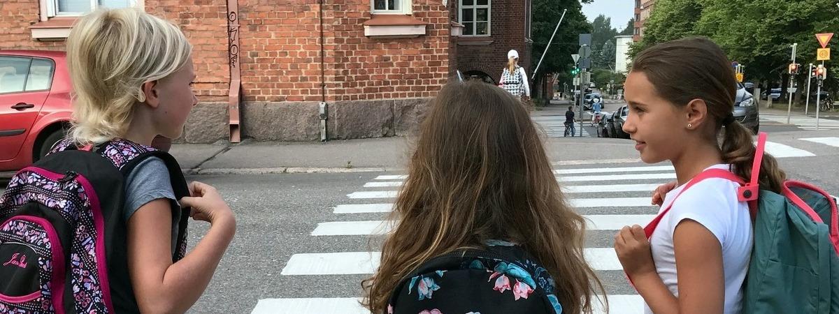 Kolme tyttöä reput selässä ylittämässä suojatietä.