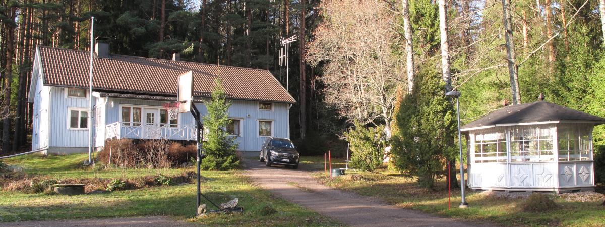 Vaaleansininen omakotitalo ja talon pihapiiri.