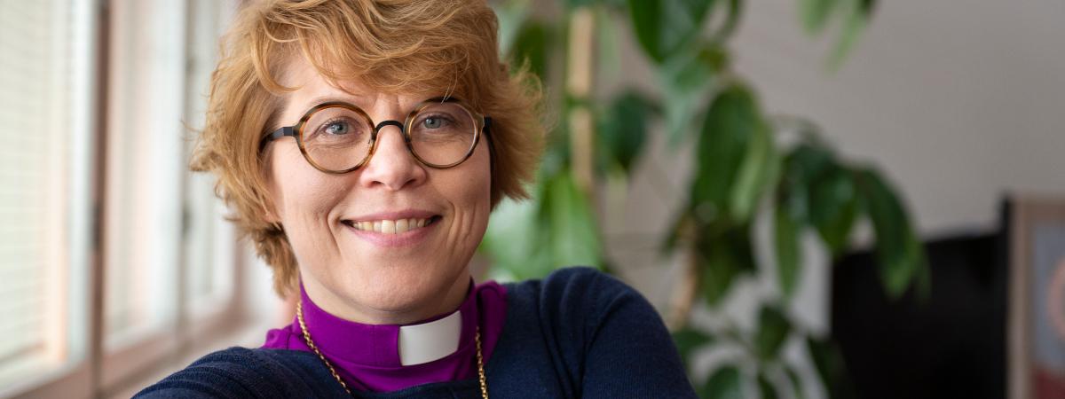 Kaisamari Hintikka. Naisella on yllään violetti paita ja papinkaulus.