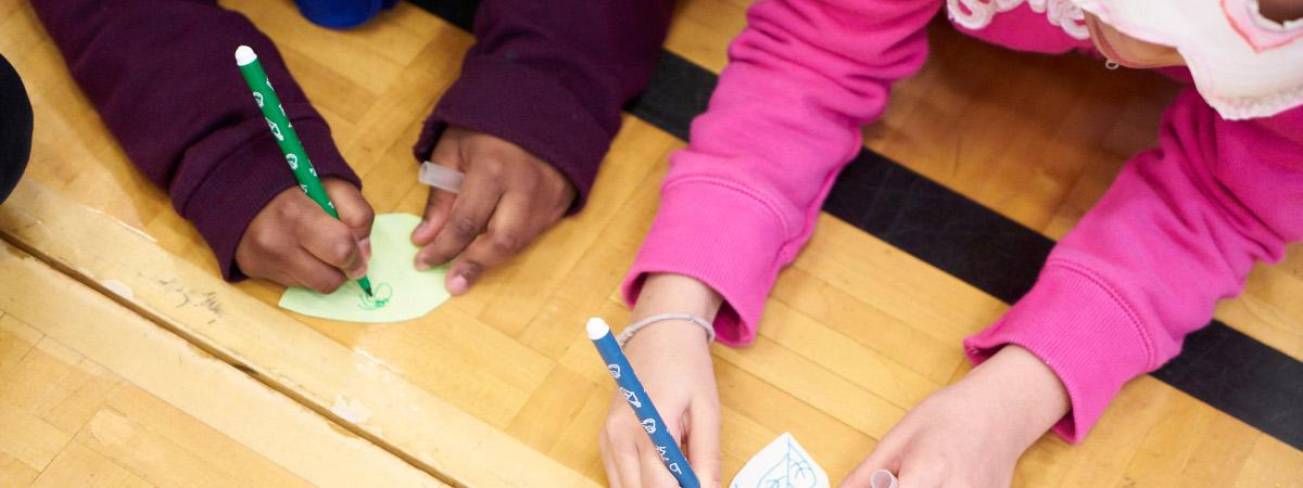 Kaksi lasta piirtävät paperinpaloille.