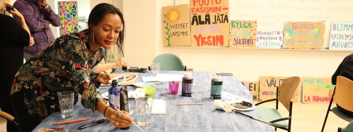 Nainen maalaa. Pöydällä maalausvälineitä, seinällä maalattuja kylttejä.