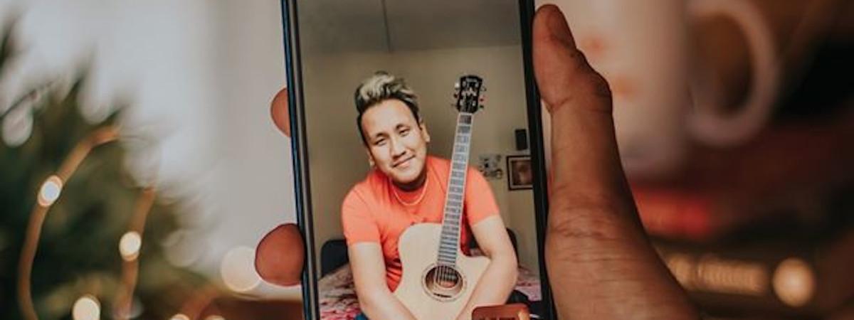 Käsi pitelee puhelinta. Puhelimessa mies hymyilee kitara sylissään.