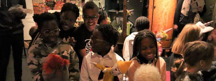 Hymyileviä adoptoituja lapsia kerhossa. Osa pitelee käsissään nukkea.