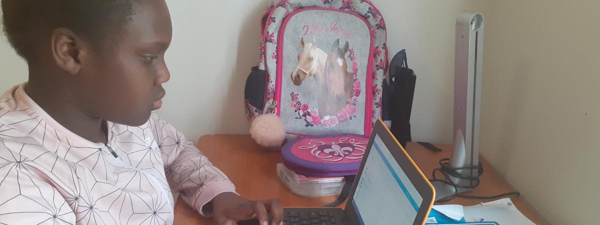 Tummaihoinen tyttö työpöydän ääressä ja katsoo kannettavan tietokoneen näyttöä.