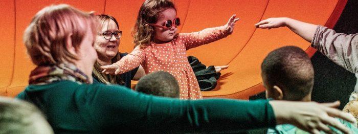 Pieni tyttö kädet levällään, aurinkolasit väärin päin silmillä. Ympärillä lapsia ja aikuisia.