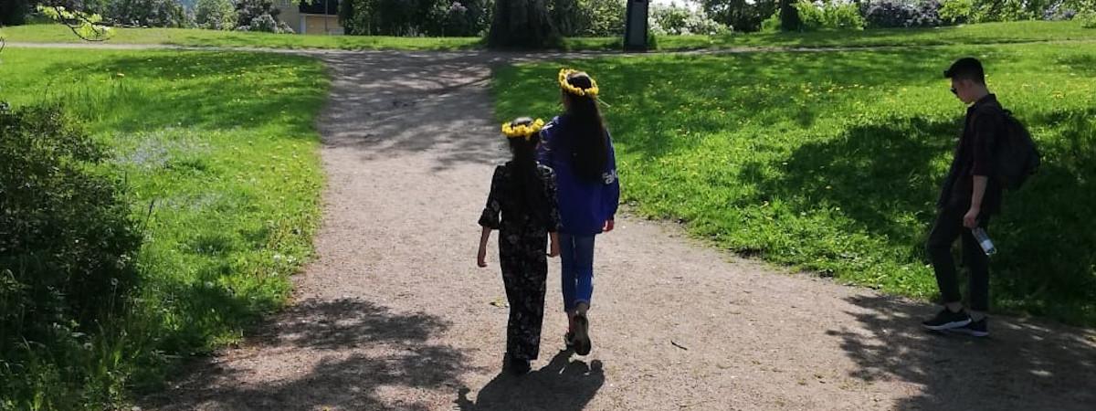 Kaksi tyttöä kulkee hiekkatietä pitkin kukkaseppeleet päässä.