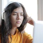 Keltapaitainen tyttö kuulokkeet korvillaan tietokoneen ääressä.