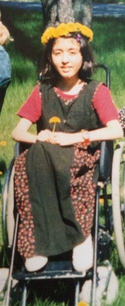 Tyttö istuu pyörätuolissa kukkaseppele päässään.