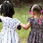 Kaksi pientä tyttöä ulkona mekot yllään.