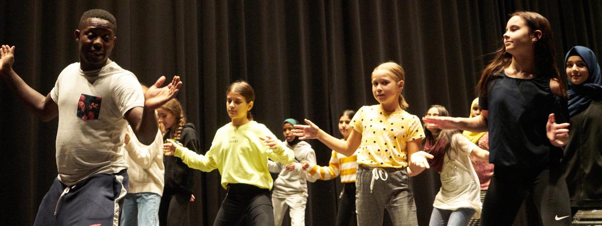 Aikuinen ja ryhmä lapsia tanssimassa.