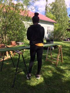 Nainen maalaamassa penkkiä.