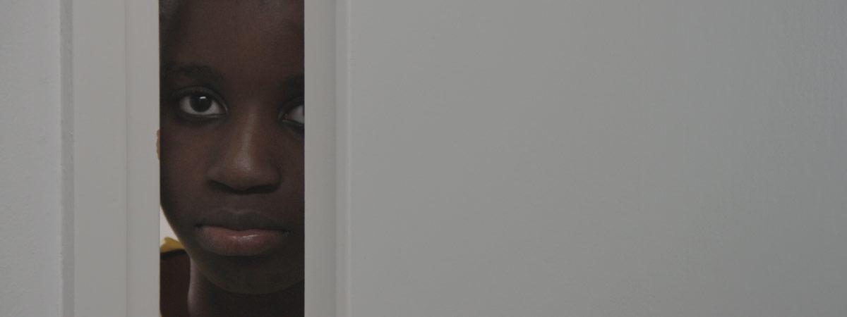Tummaihoinen poika kurkistaa ovenraosta.