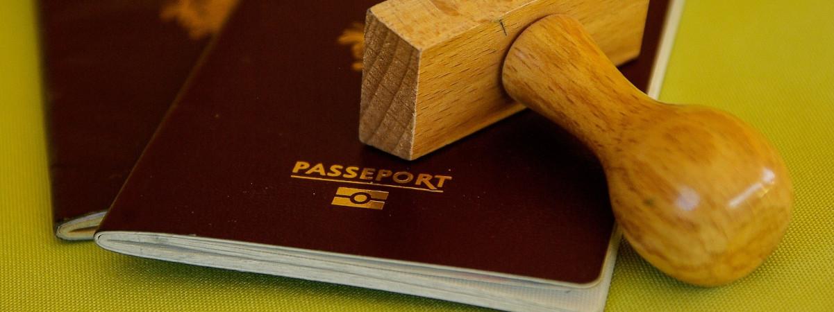 Kaksi passia ja puinen leimasin.