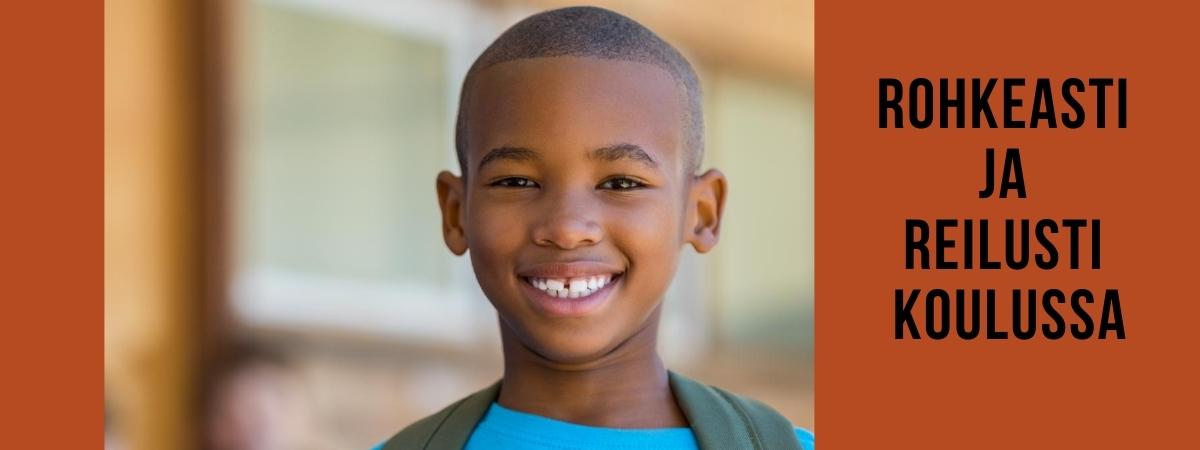 Tummaihoinen poika hymyilee leveästi.