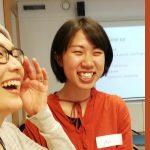 Kaksi aasialaistaustaista nauravaa ihmistä.