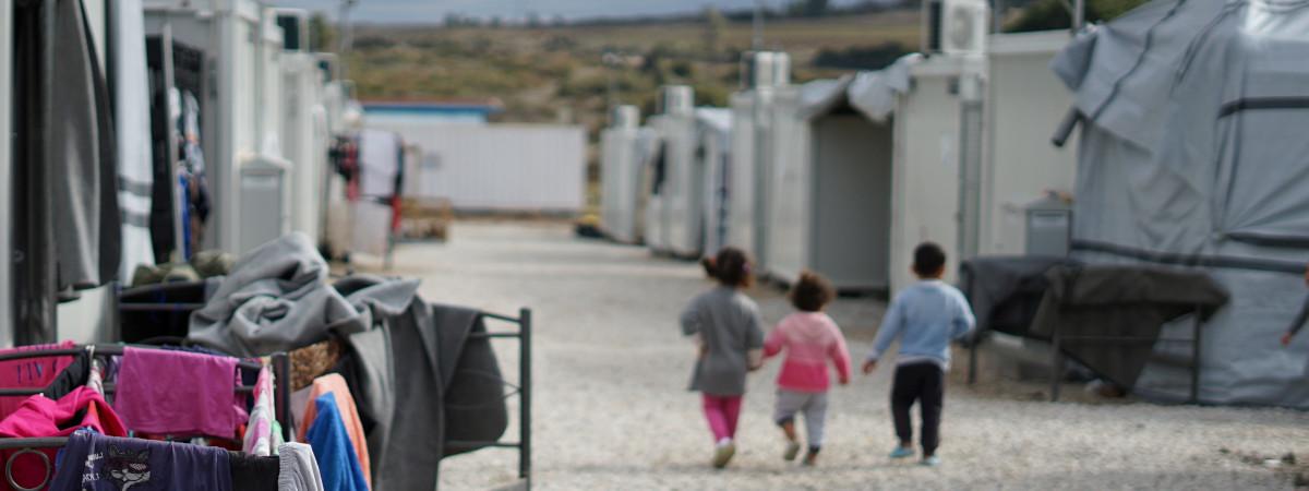 Kolme lasta kävelevät vierekkäin pakolaisleirillä.