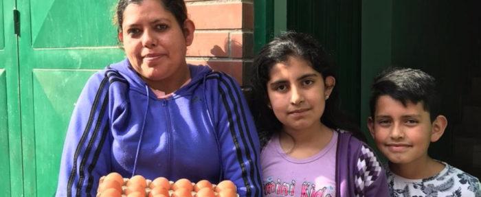 Kuvassa on nainen, joka kantaa kananmunia, sekä kaksi lasta.