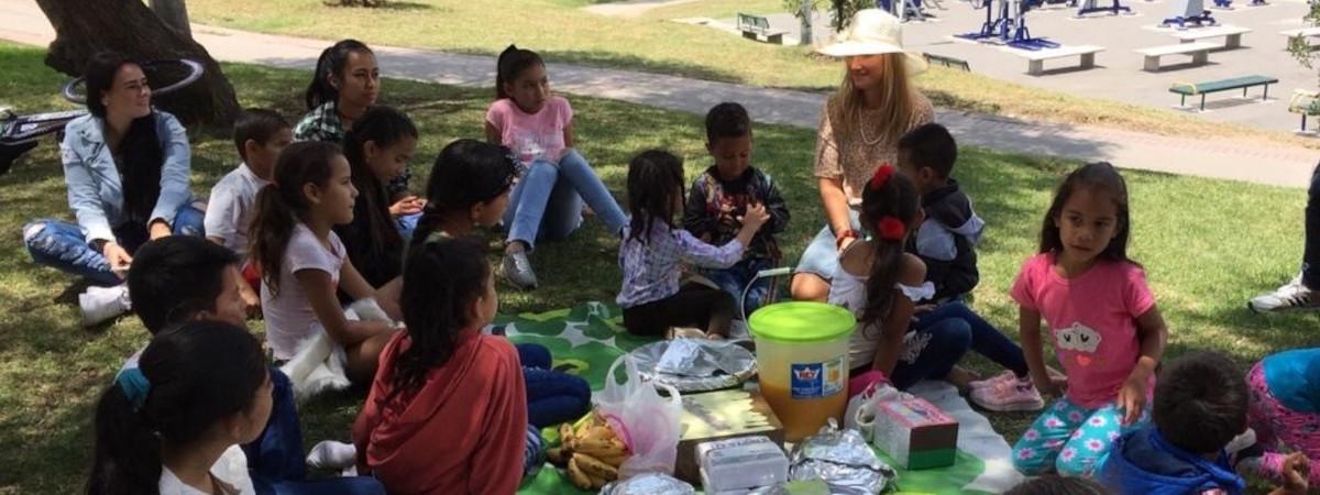 Kolumbialaisia lapsia nurmikolla syömässä välipalaa.