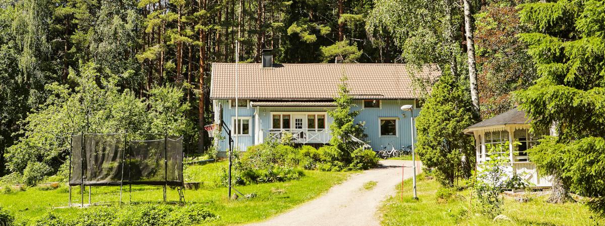 Monikulttuurinen Koti Ilolan vaaleansininen talo ja vehreä pihapiiri.
