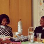 Afrikkalaistaustaisia adoptoituja tyttöjä pöydän ääressä mikrofonin ympärillä.