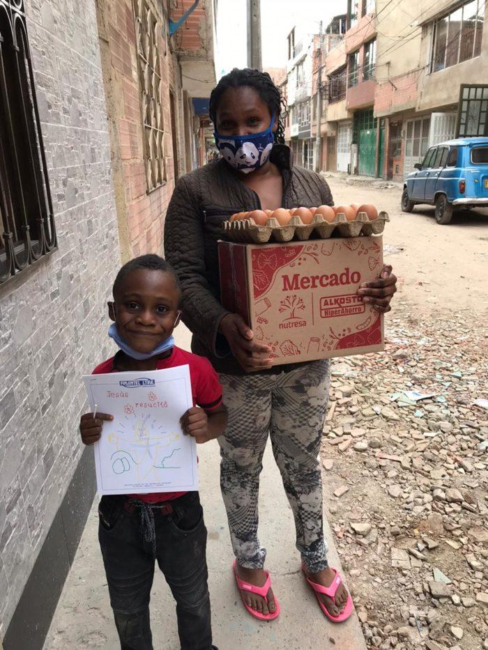 Nainen kantaa pahvilaatikkoa ja kananmunakennoa. Vieressä poika pitelee piirrustusta kameraa kohti.