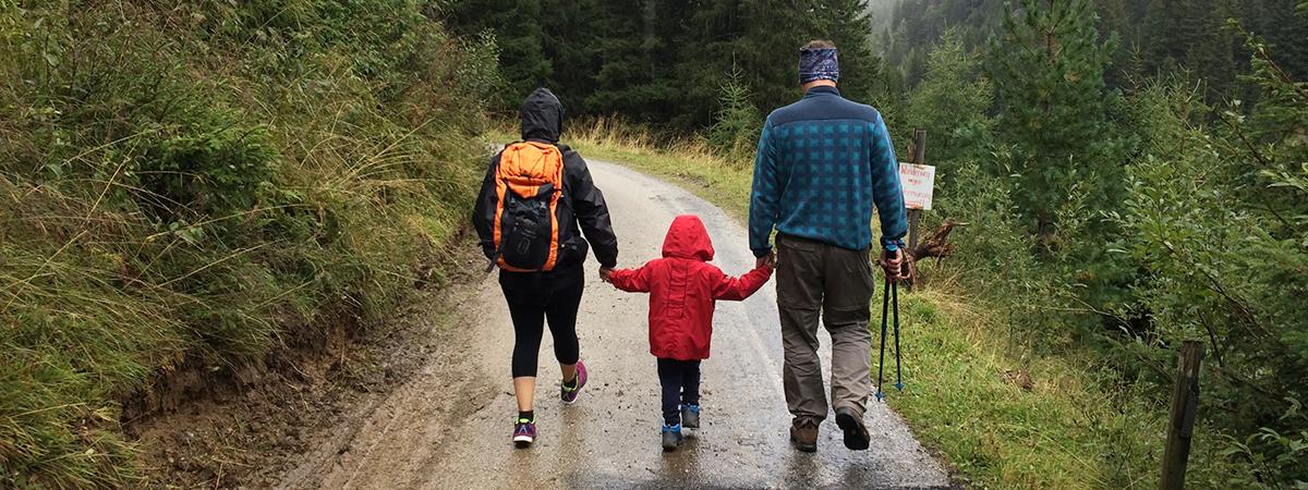 Perhe kävelee tietä pitkin metsän keskellä.