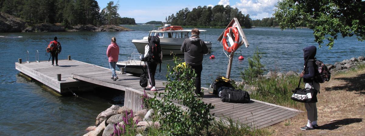 Ihmisiä laiturilla matkatavaroiden kanssa aurinkoisena päivänä. Vene on saapumassa laituriin.