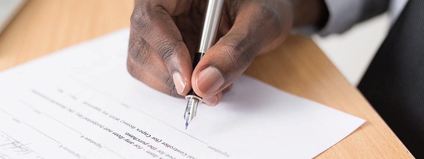 Lähikuva, jossa käsi allekirjoittaa paperia.