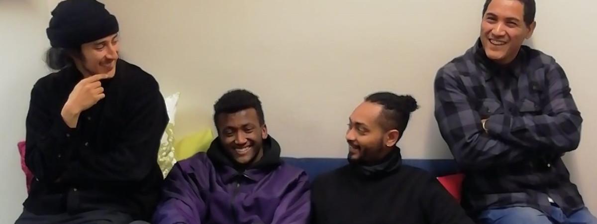Neljä miestä istuu sohvalla ja hymyilee.