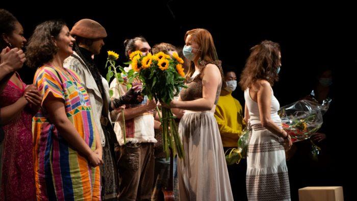 Näyttelijät lavalla esityksen jälkeen. Nainen jakaa näyttelijöille kukkakimppuja.