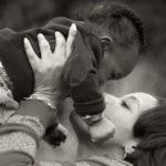 Nainen (äiti) nostaa pientä lasta korkealle ylöspäin.