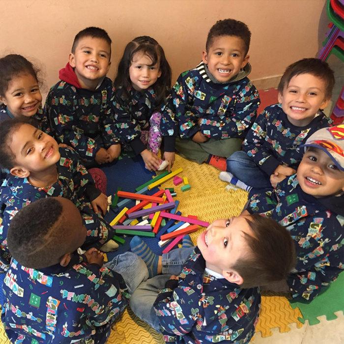 Kolumbialaisia lapsia istumassa piirissä samanlaiset kouluvaatteet yllään.