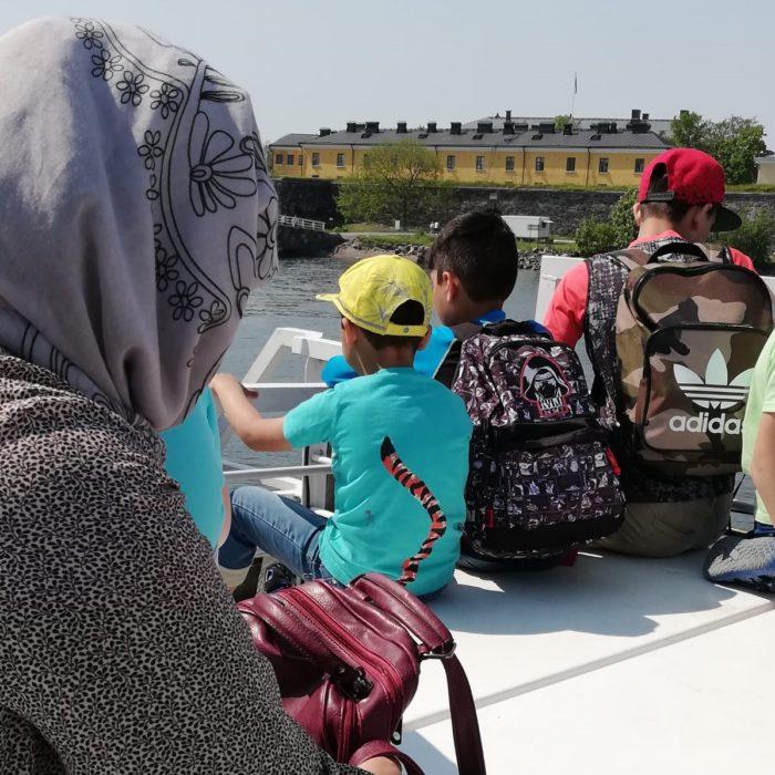 Maahanmuuttajaperhe (nainen ja kolme nuorta poikaa) istuvat lautalla aurinkoisena päivänä.
