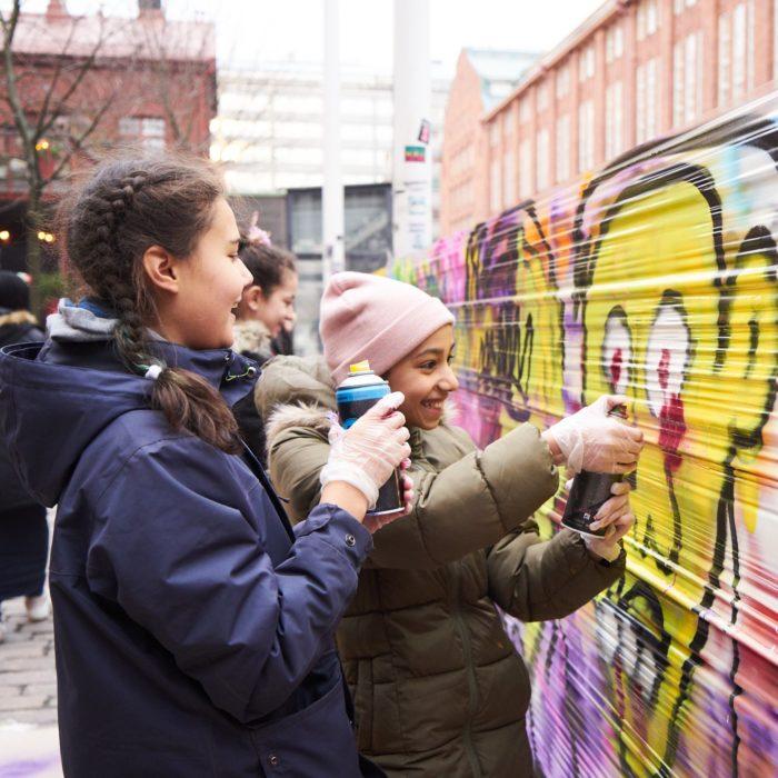 Lapsia maalaamassa graffititaidetta.