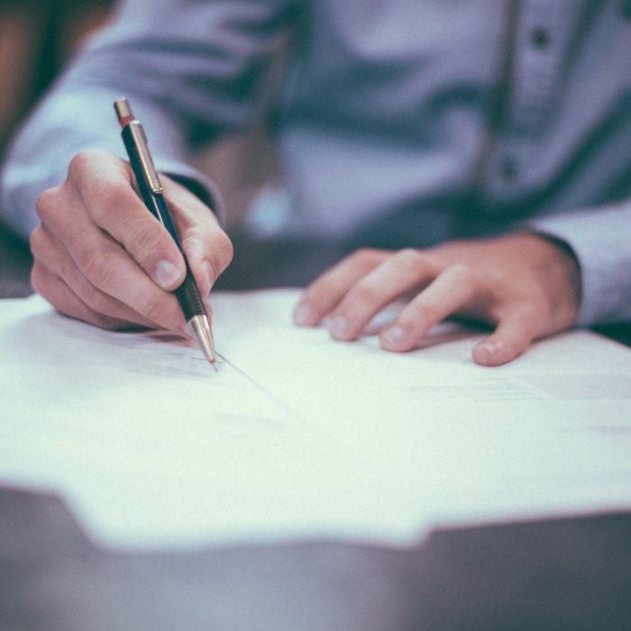 Papereita pöydällä. Kuvassa näkyy kädet allekirjoittamassa papereita.