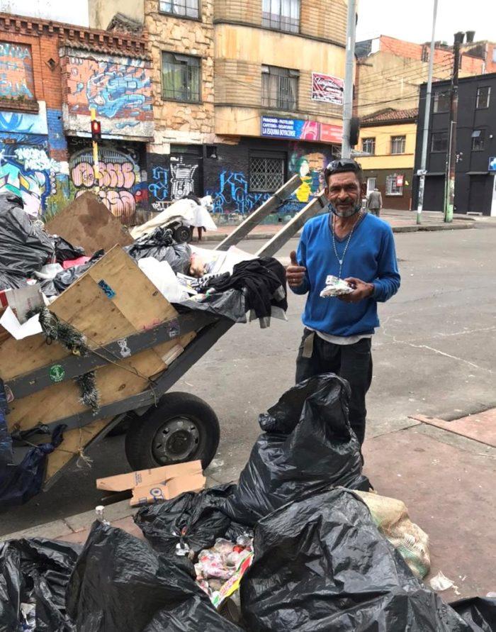 Mies isojen kottikärryjen ja roskapussien kanssa jalkakäytävän reunalla Bogotan kaupungissa Kolumbiassa.