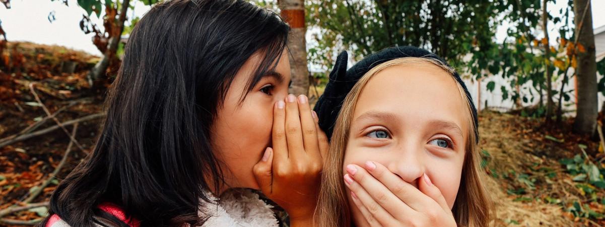 Kaksi tyttöä kuiskuttelevat ja nauravat.