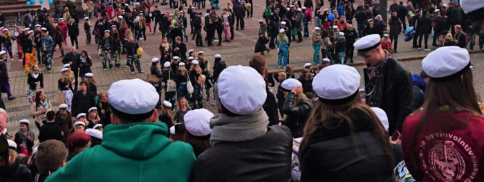 Nuoria ylioppilaslakit päässä istumassa portailla.