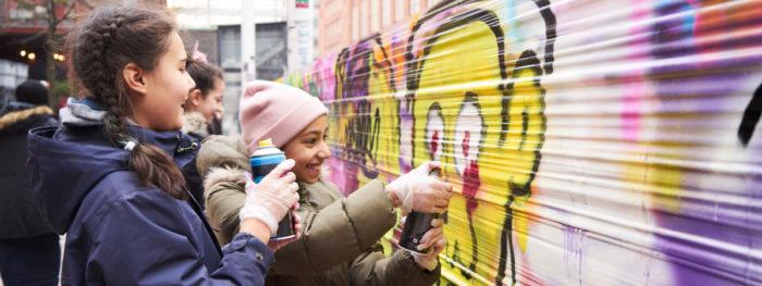 Kaksi tyttöä maalaa graffitiseinää.
