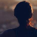 Nuori nainen istuu rannalla auringonlaskussa.